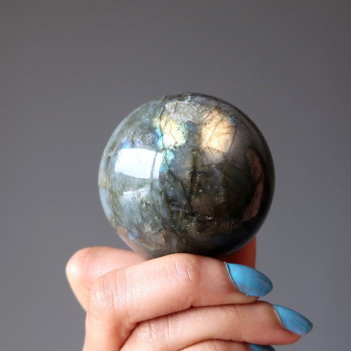hand holding up a rainbow labradorite sphere