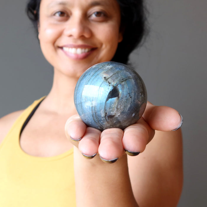 sheila of satin crystals holding a blue flash labradorite sphere