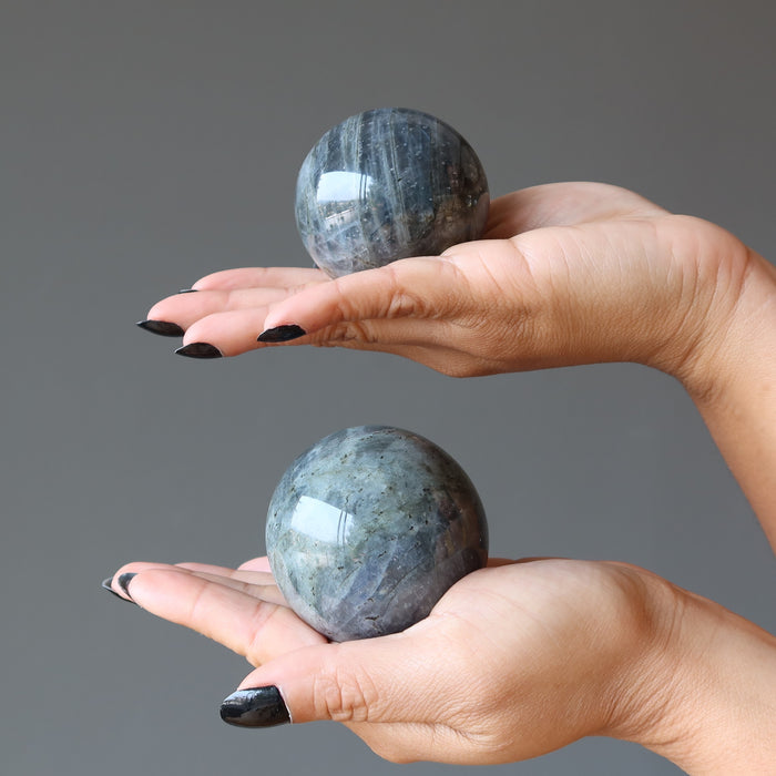 two hands each holding labradorite spheres in the palms