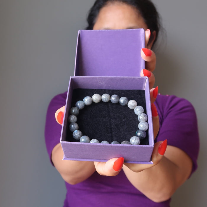 sheila of satin crystals holding a gift box with a faceted labradorite beaded stretch bracelet inside