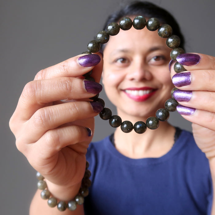 sheila of satin crystals wearing and showing off a round labradorite beaded stretch bracelet