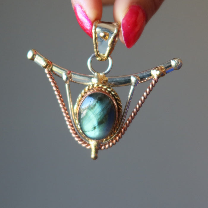 hand holding labradorite pendant in front of female chest