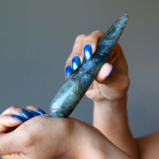 hand holding labradorite massage wand massaging wrist
