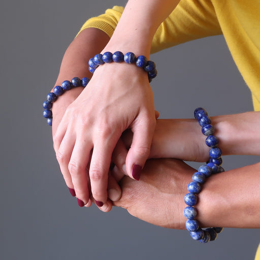 man and women's four hands intertwined wearing lapis lazuli stretch bracelets