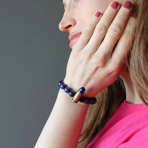 hand on face hand on leg wearing a lapis peace bullet stretch bracelet