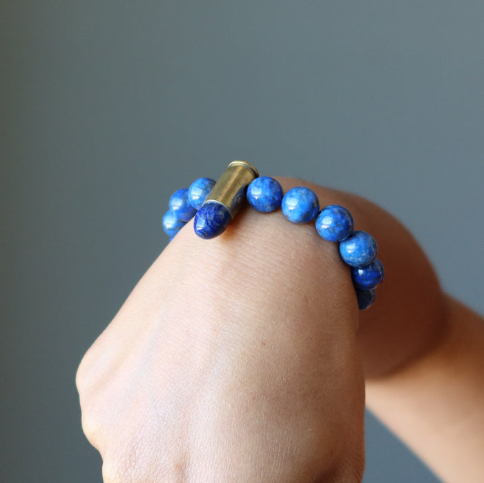 hand making a fist wearing a lapis peace bullet stretch bracelet