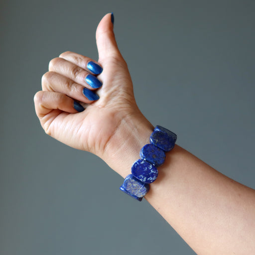 hand giving a thumbs up wearing rounded rectangle lapis beaded stretch bracelet