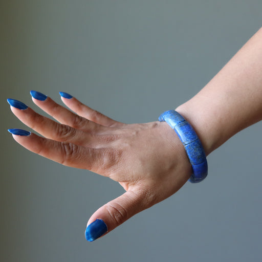 hand wearing wide lapis lazuli stretch bracelet