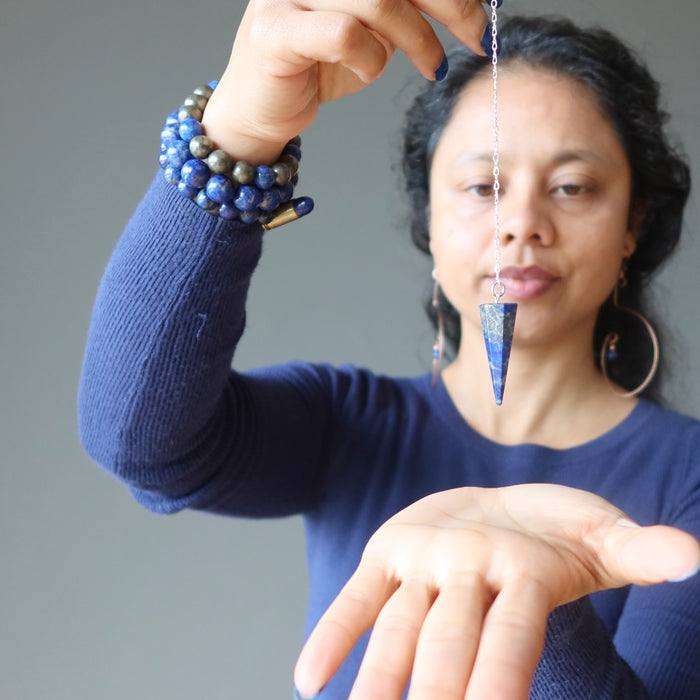 sheila of satin crystals holding a lapis lazuli sterling silver pendulum over her palm for dowsing