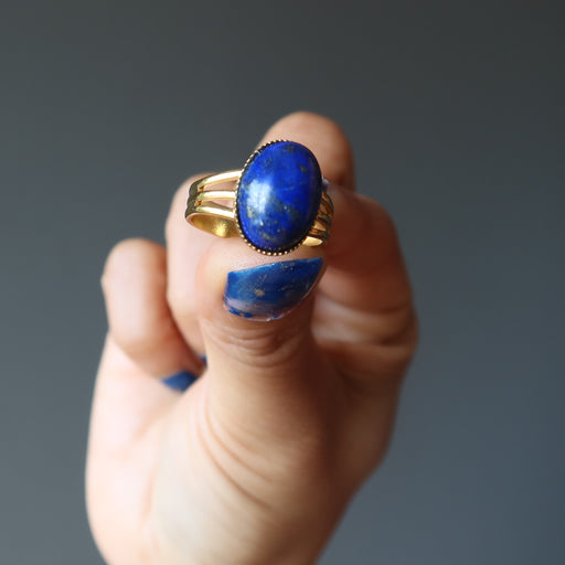 hand holding lapis lazuli gemstone in gold tone adjustable ring