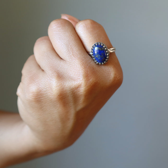 fisted hand wearing lapis lazuli sterling silver ring adjustable jewelry on the pointer finger