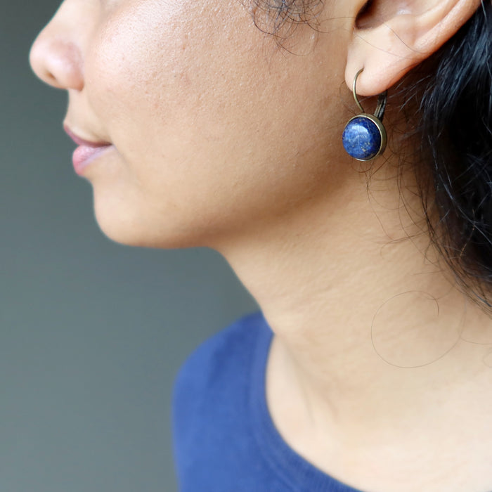 on ear wearing round lapis lazuli in antique bronze leverback earrings