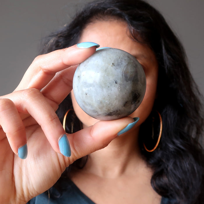 sheila of satin crystals holding a labradorite sphere in front of her face