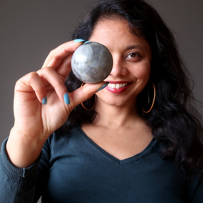 sheila of satin crystals holding up a labradorite sphere
