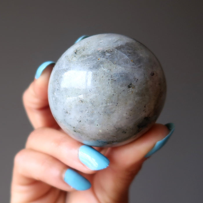hand holding up a silver labradorite sphere