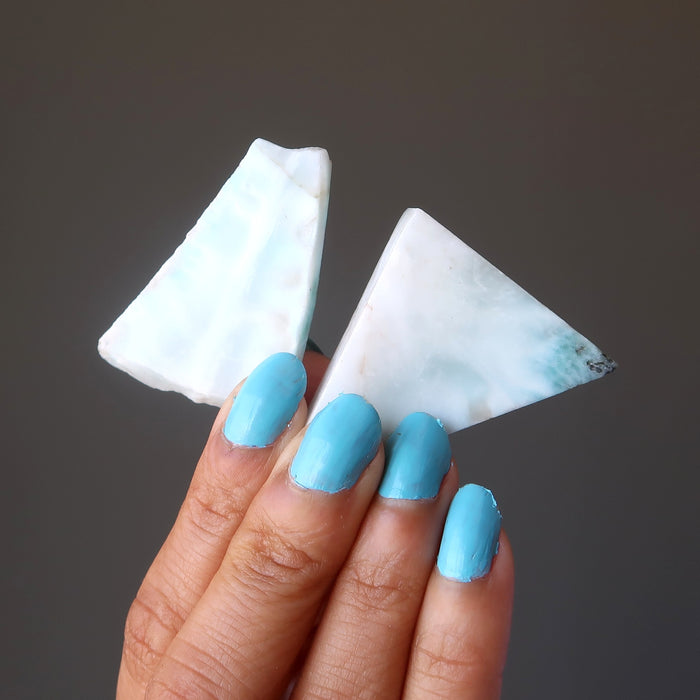 hand holding pair of triangular larimar slabs