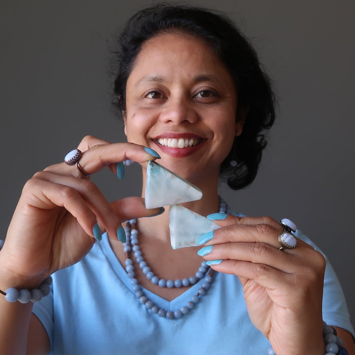 sheila of satin crystals holding pair of triangular larimar slabs at her throat chakra