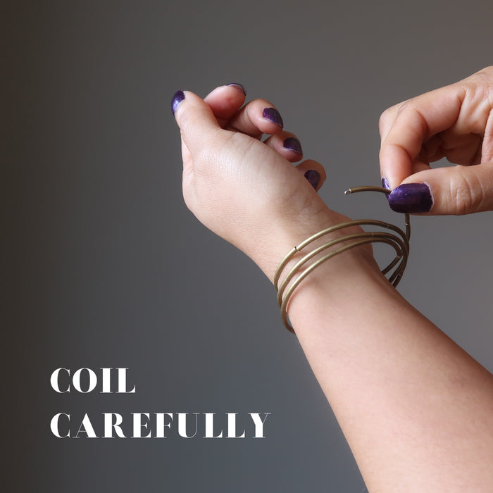 "hand coiling red lava coil bracelet on a wrist with a sign saying ""coil carefully"""