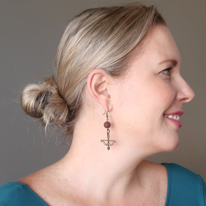 liz of satin crystals wearing red lava bow and arrow archery dangle earrings