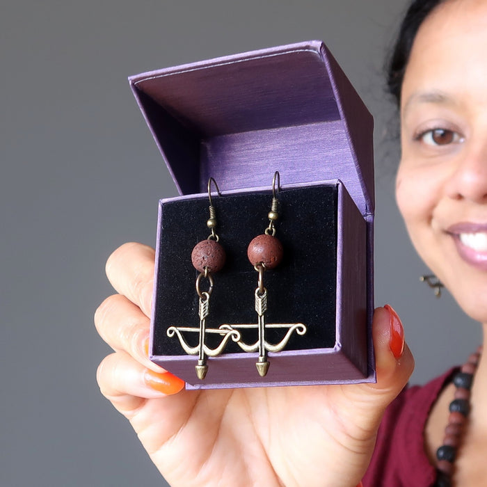 of satin crystals wearing red lava bow and arrow archery dangle earrings in purple gift box