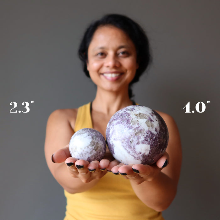sheila of satin crystals holding two lepidolite spheres to show size difference