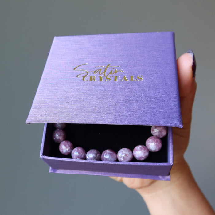 a round beaded purple lepidolite bracelet in a satin crystals purple box