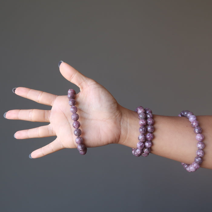 An arm showcasing four purple lepidolite stretch bead bracelets
