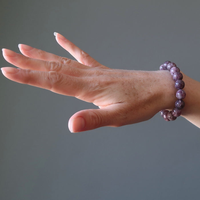 A lady's hand outstretched to display the round beaded purple lepidolite stretch bracelet