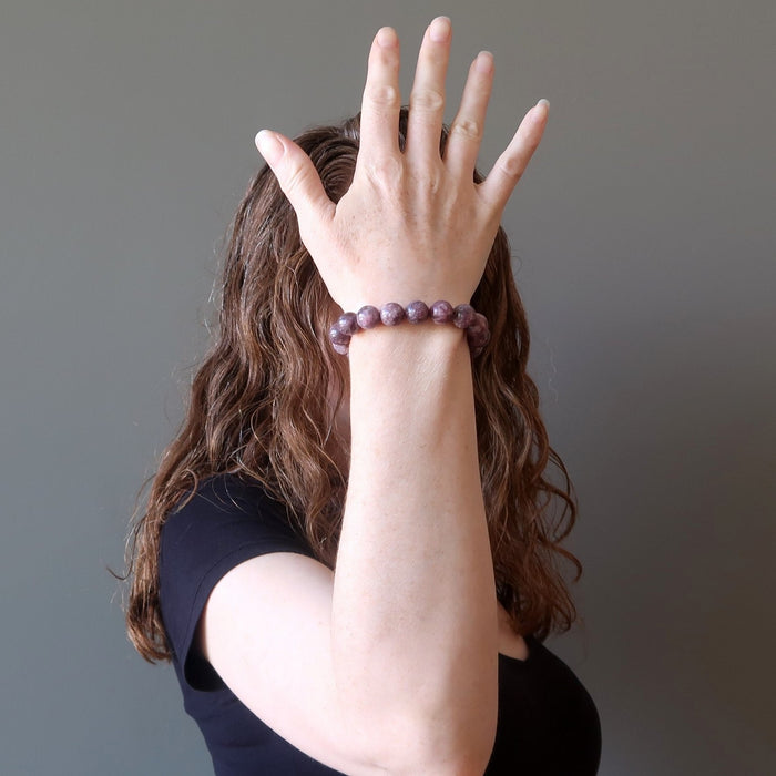 A female model shows off a purple lepidolite healing crystal bracelet on her wrist