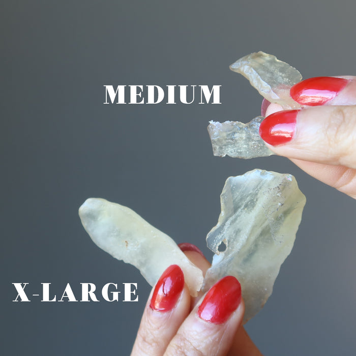 hands holding two pairs of libyan desert glass to show difference between medium and x-large sizes