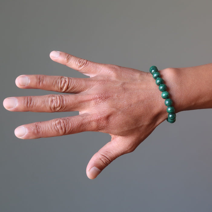man's hand wearing green malachite bracelet