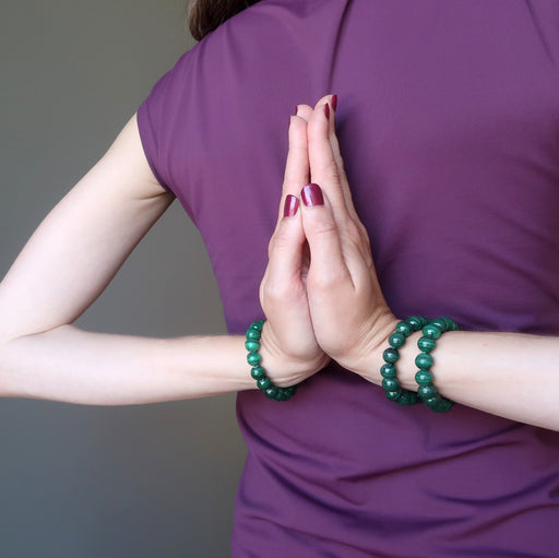 female model with hands in prayer at her back wearing three green malachite stretch bracelets