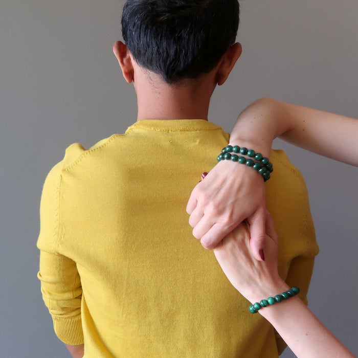 women's hands on man's back featuring 3 malachite bracelets