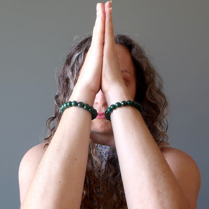 aleks of satin crystals with hands in meditation wearing malachite bracelets on each wrist