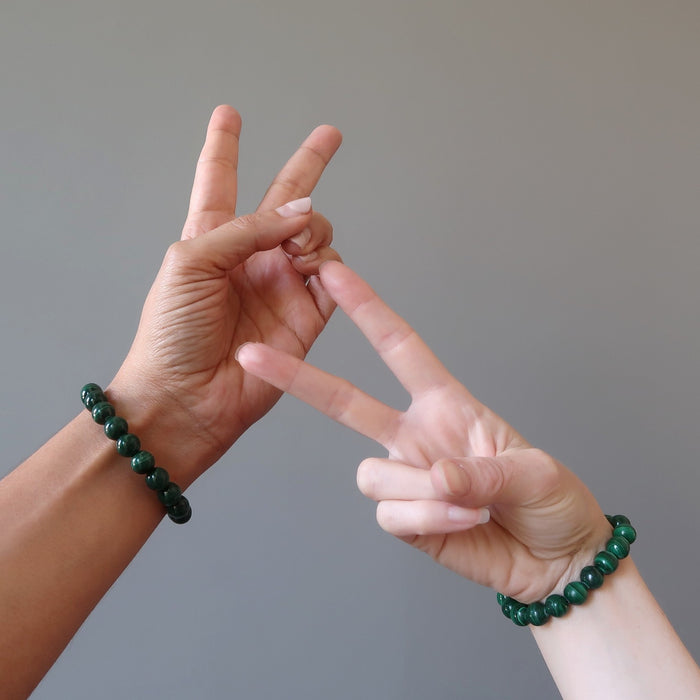 man and woman's hands making peace signs wearing green malachite bracelets