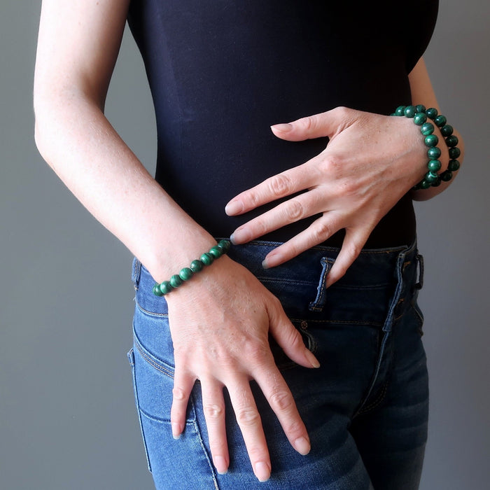 woman with hands at torso wearing malachite bracelets