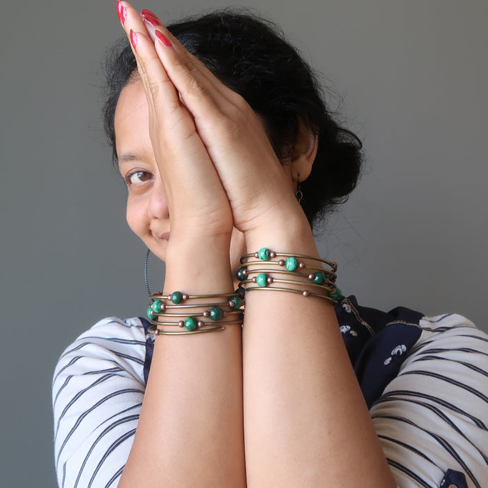 Sheila of Satin Crystals with hands in prayer to show both arms adorned with the green malachite gemstone memory wire bracelet