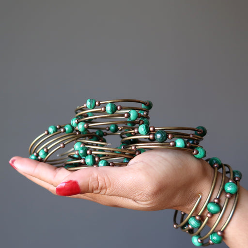 A hand holding 4 Malachite Accordion of Love bracelets, and wearing one more