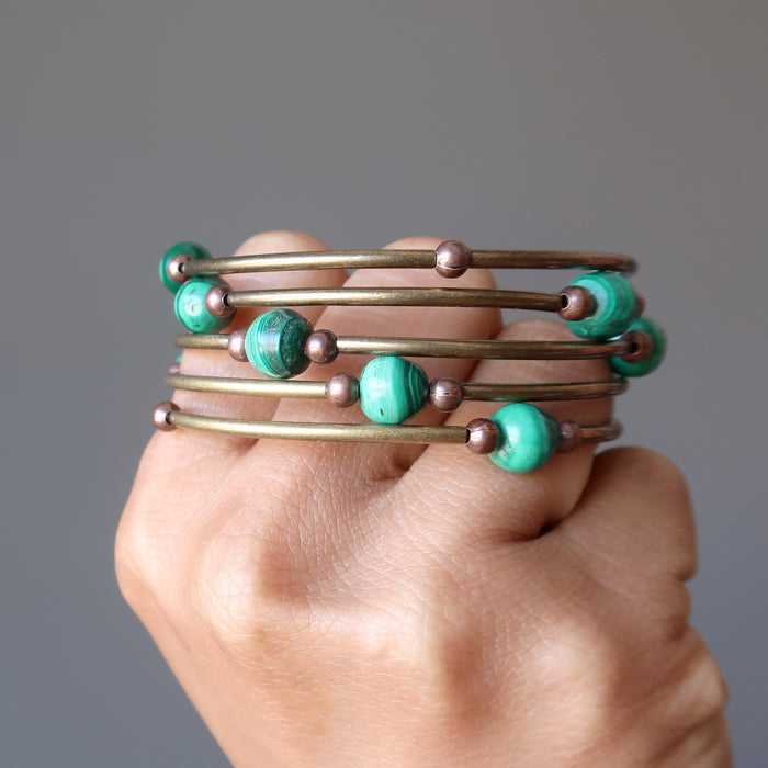A hand holding the Satin Crystals Malachite coil bracelet