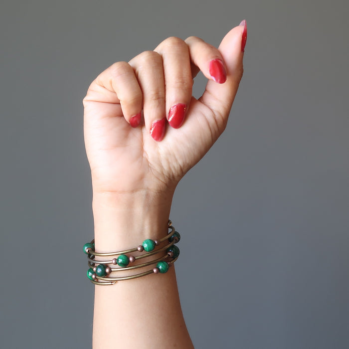 A woman's hand and arm showing off the Malachite vintage coil bracelet