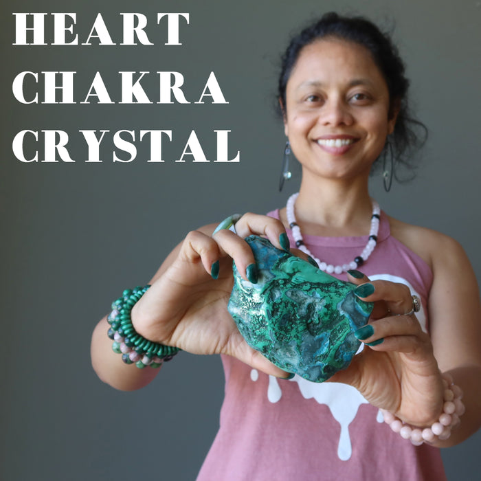 sheila of satin crystals holding a malachite chrysocolla polished cluster in front of her heart chakra