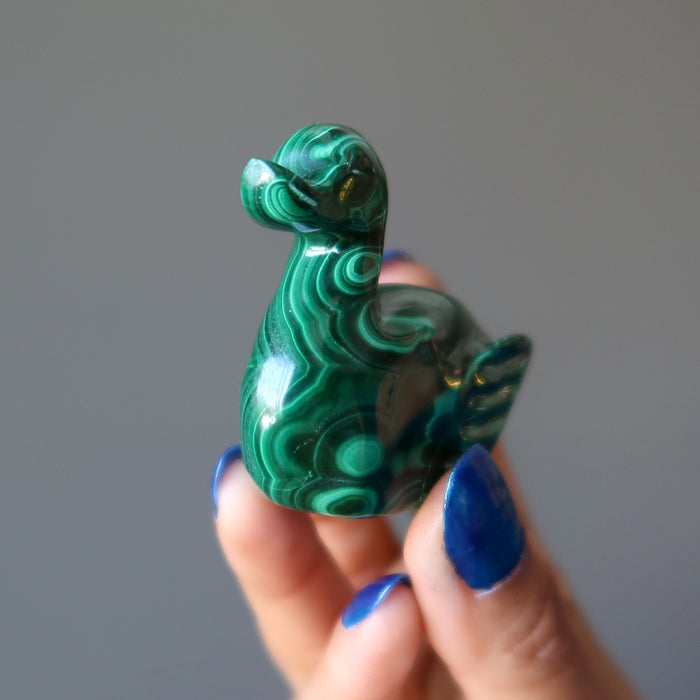 hand holding malachite duck carving