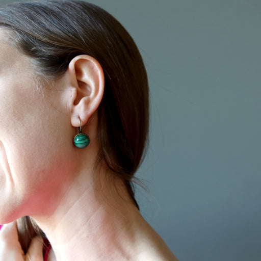 holly of satin crystals wearing malachite stones in antique leverback earrings