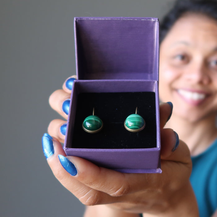 sheila of satin crystals holding a gift box with malachite bronze leverback earrings