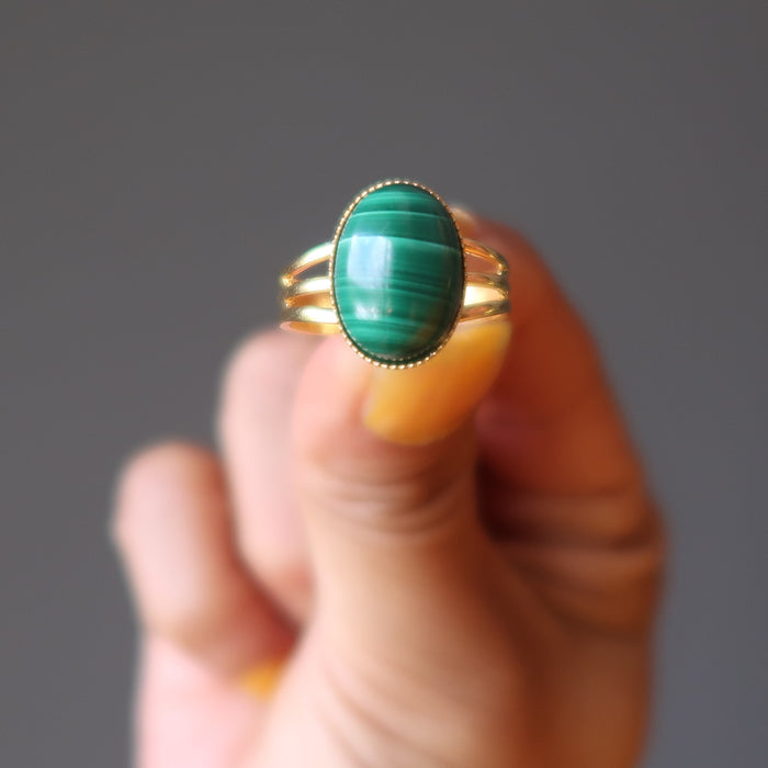 hand holding green oval malachite in gold adjustable ring