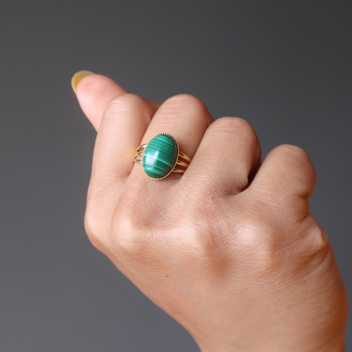 hand wearing green oval malachite in gold adjustable ring