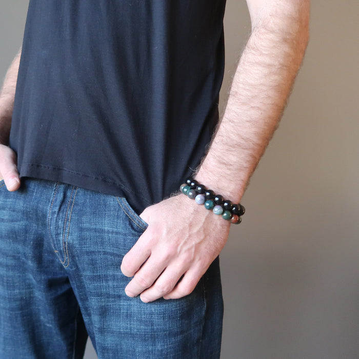 male hand in jeans pocket modeling bloodstone and rainbow obsidian bracelet set
