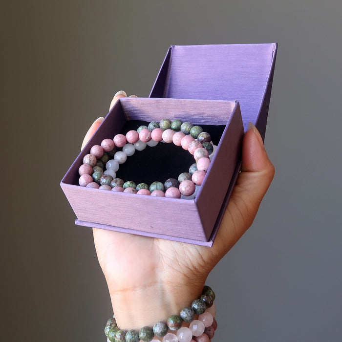 hand wearing and holding chrysocolla cuprite, rose quartz, rhodonite bracelet set in purple gift box