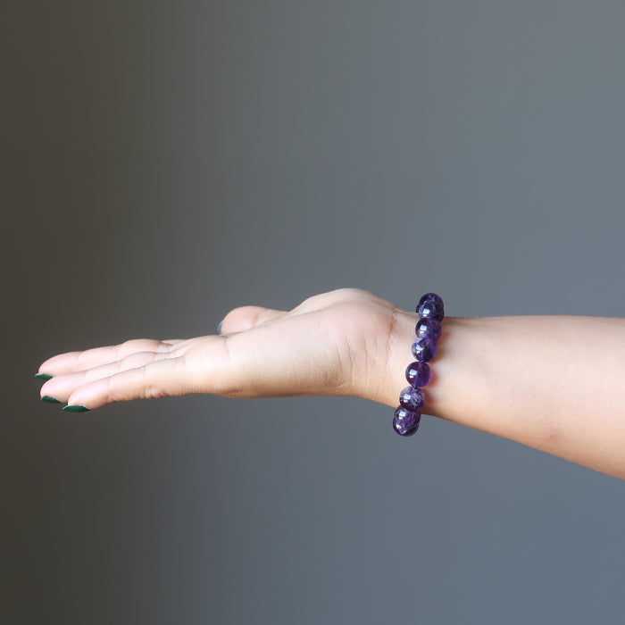female hand wearing amethyst bracelet