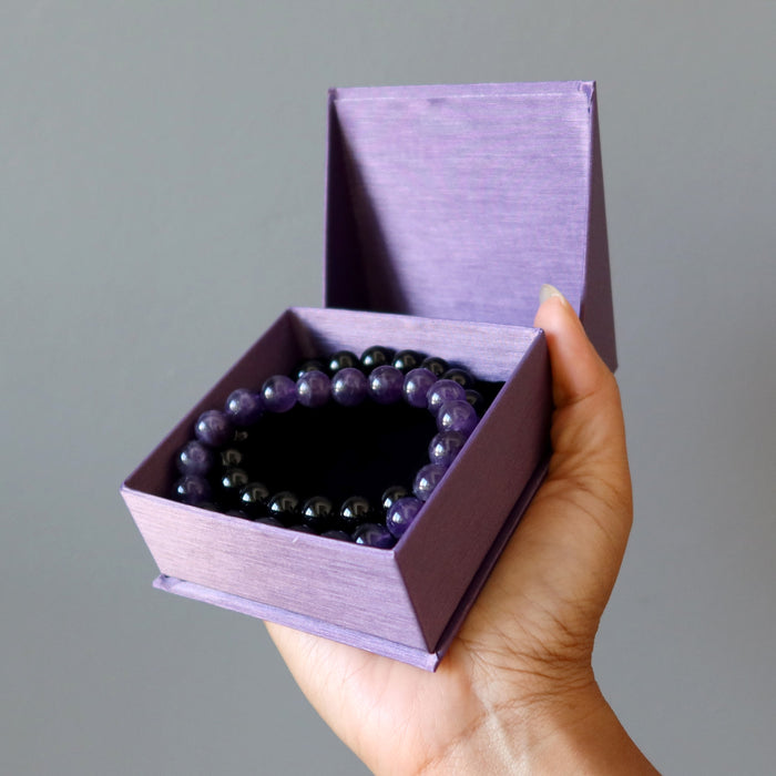 female hand holding gift box with black tourmaline and amethyst bracelet set